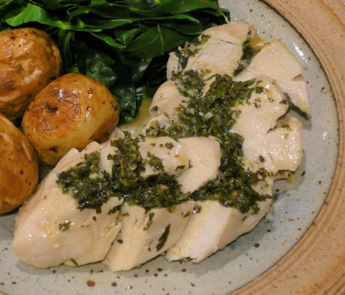 A dish of garlic & herb chicken with oven roast potatoes & greens